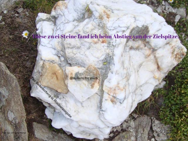 Zwei Steine und zwar ein Herzstein aus weißem Fels und ein Stein, wie die Zielspitze mit einer sieben drin