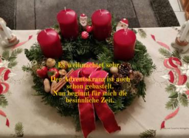 Der Adventskranz, gebunden aus Tannenzweigen, geschmückt mit roten Kerzen steht auf dem Tisch und wartet darauf, dass die erste Kerze entzündet wird.